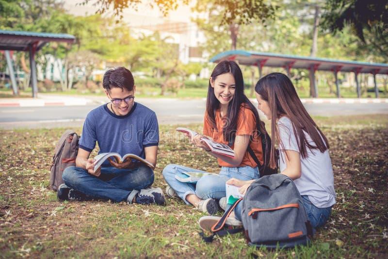 Grupo de livros de leitura asi?ticos da estudante universit?rio e classe especial do tutoria para o exame no campo de grama em fo imagem de stock