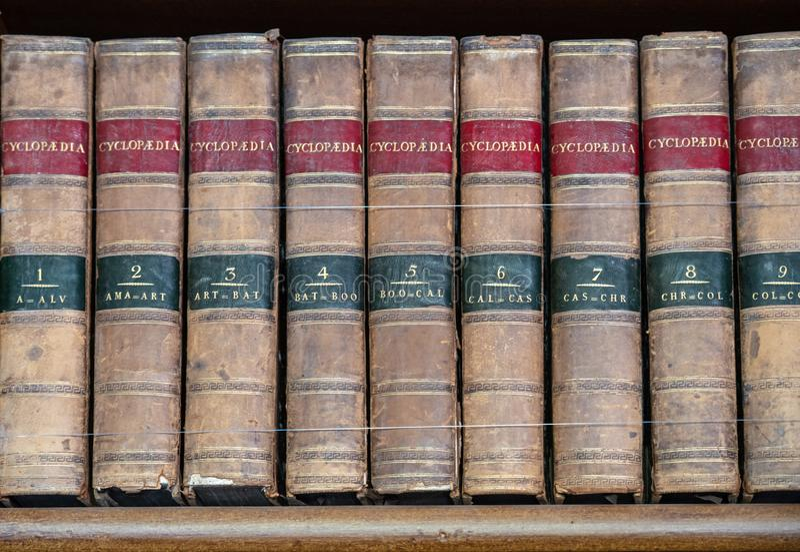 Grupo de livros de referência velhos em uma prateleira fotos de stock