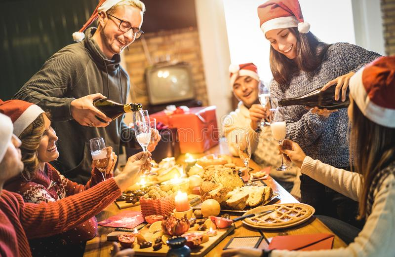 Grupo de los amigos con los sombreros de santa que celebra en el partido de cena de la Navidad fotografía de archivo libre de regalías