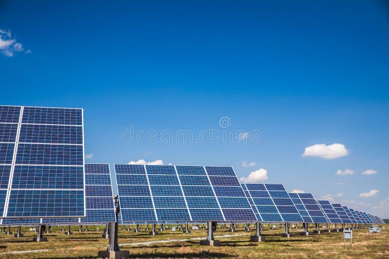 Grupo de los paneles solares en un cielo azul con las nubes foto de archivo libre de regalías