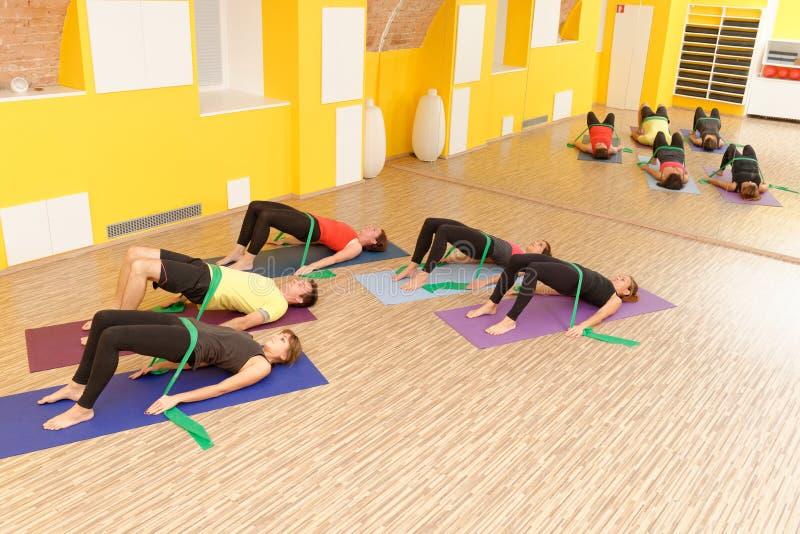Grupo de los pilates de los aeróbicos con las gomas foto de archivo