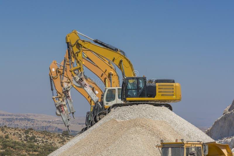Grupo de máquinas escavadoras no monte do cascalho fotos de stock royalty free