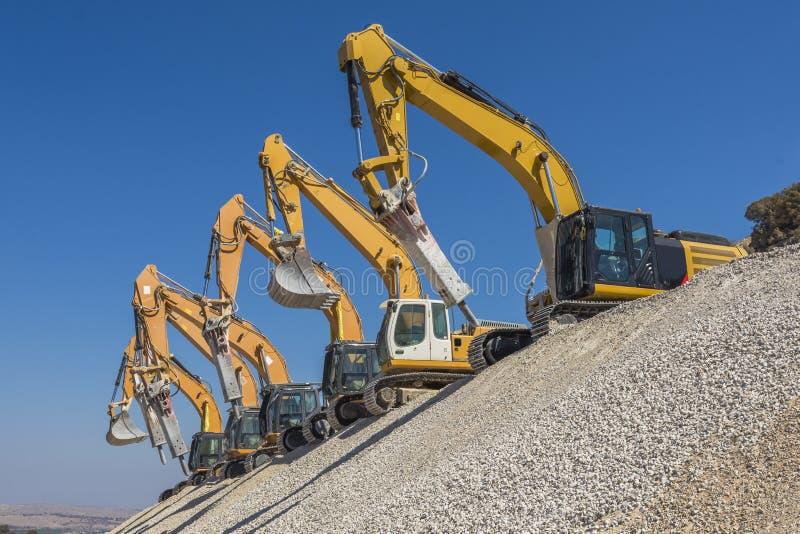 Grupo de máquinas escavadoras no monte do cascalho imagem de stock royalty free