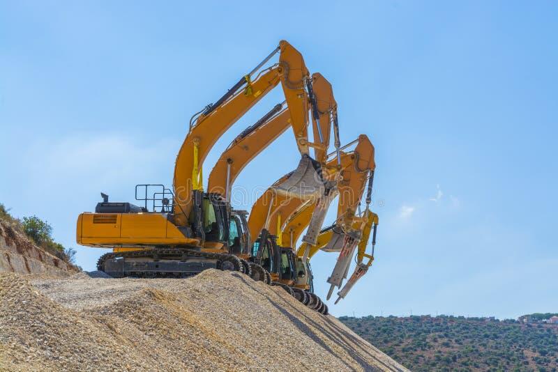 Grupo de máquinas escavadoras no monte do cascalho imagem de stock