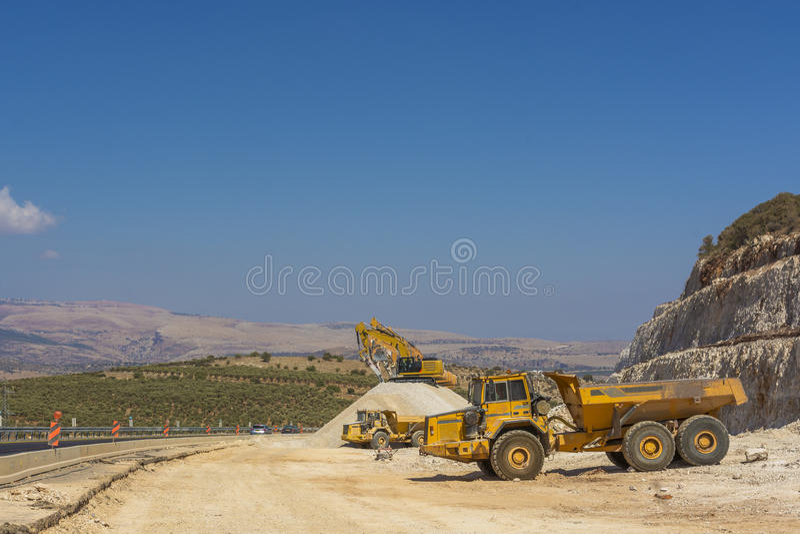 Grupo de máquinas escavadoras no monte do cascalho fotos de stock