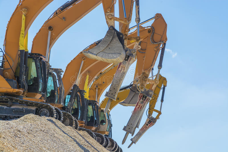 Grupo de máquinas escavadoras no monte do cascalho fotografia de stock