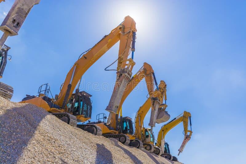 Grupo de máquinas escavadoras no monte do cascalho foto de stock