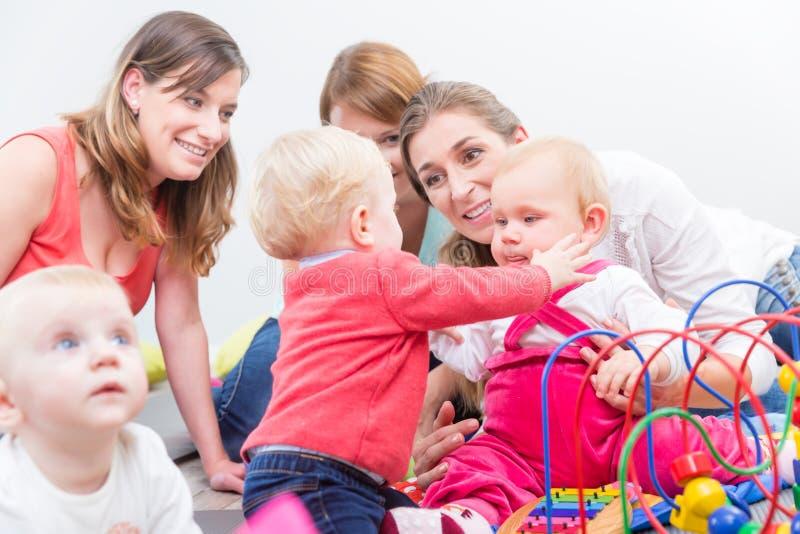 Grupo de mães novas felizes que olham seus bebês bonitos e saudáveis fotografia de stock