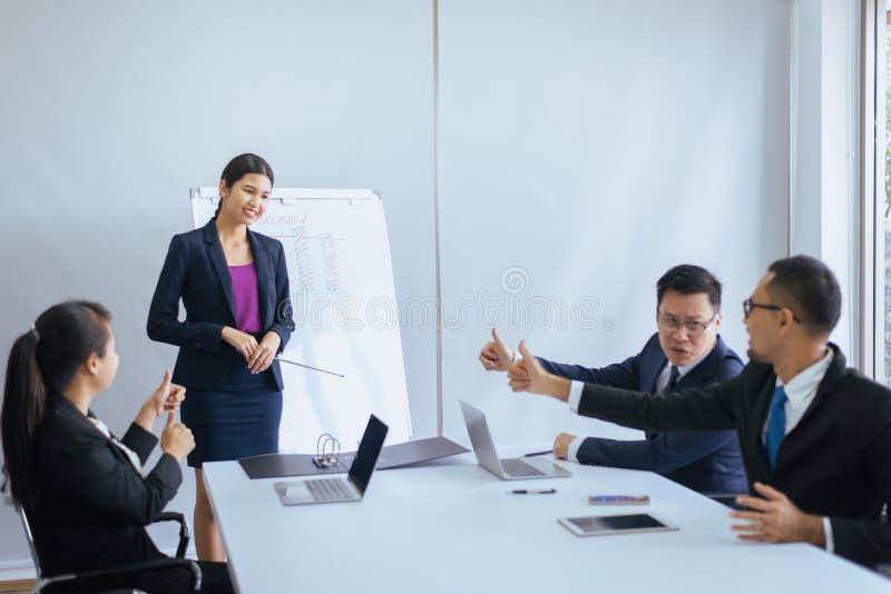 Grupo de mãos asiáticas dos povos do negócio que mostram o polegar acima após a reunião, apresentação do sucesso e treinando o se fotos de stock royalty free