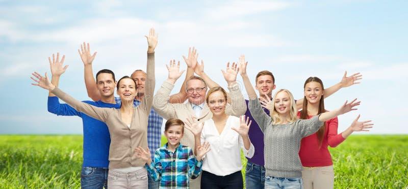 Grupo de mãos de ondulação de sorriso dos povos fotografia de stock