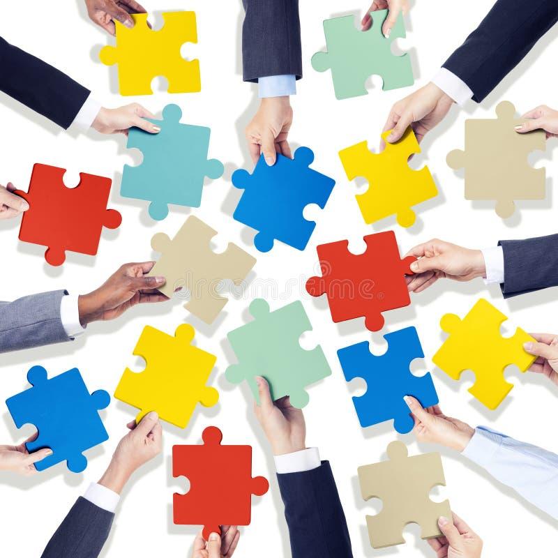 Grupo de mãos que guardam partes coloridas da serra de vaivém fotografia de stock royalty free