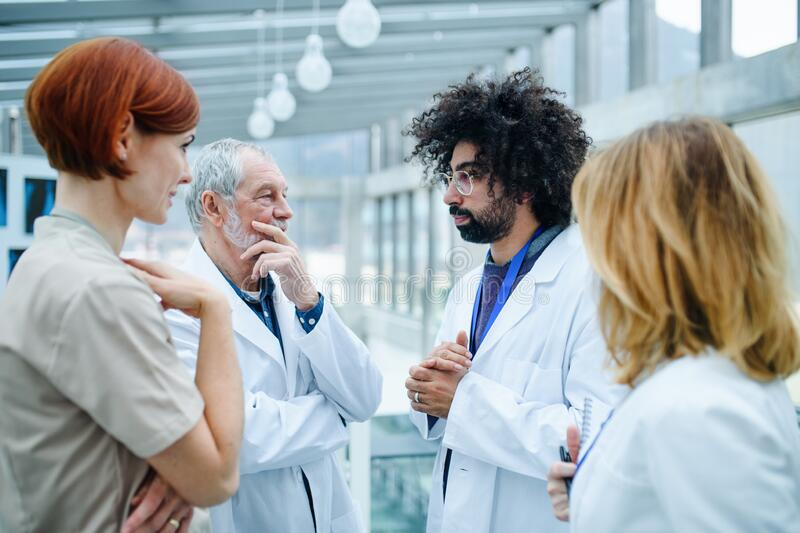 Grupo de médicos en conferencia, equipo médico hablando imagen de archivo