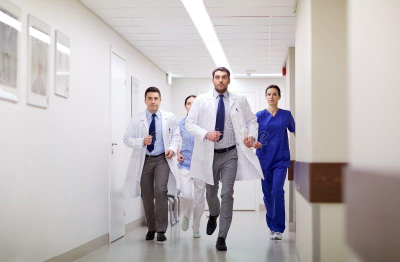Grupo de médicos que andam ao longo do hospital imagens de stock