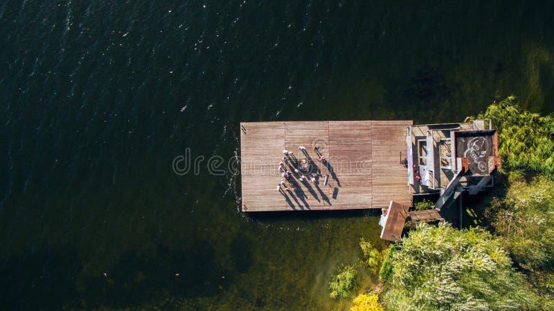 Grupo de músicos e de cantores que estão no cais velho no rio surrealism Vista de acima Silhueta do homem de negócio Cowering imagem de stock