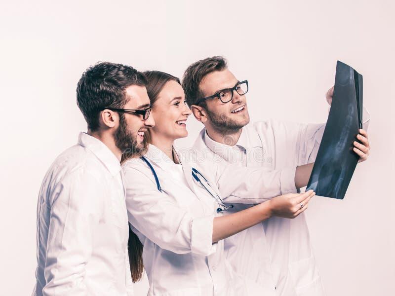 grupo de m?dicos con las radiograf?as en un fondo blanco imagen de archivo libre de regalías