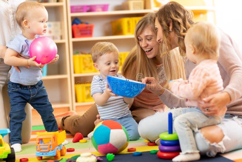 Grupo de mamáes con sus bebés en cuarto de niños fotos de archivo