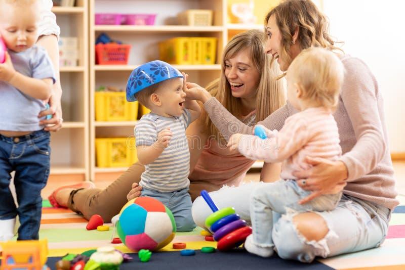 Grupo de mamãs com seus bebês no playgroup foto de stock royalty free