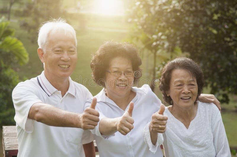 Grupo de mayores asiáticos que muestran los pulgares para arriba foto de archivo libre de regalías