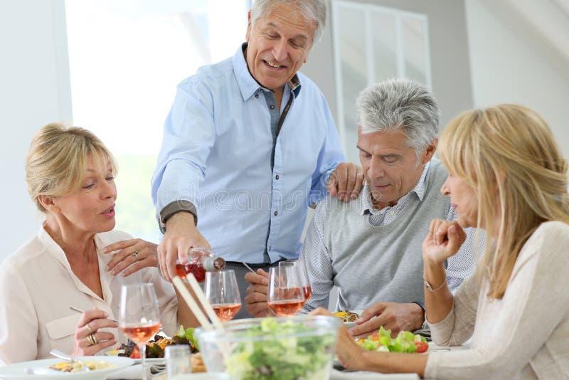 Grupo de mayores que almuerzan junto imagen de archivo