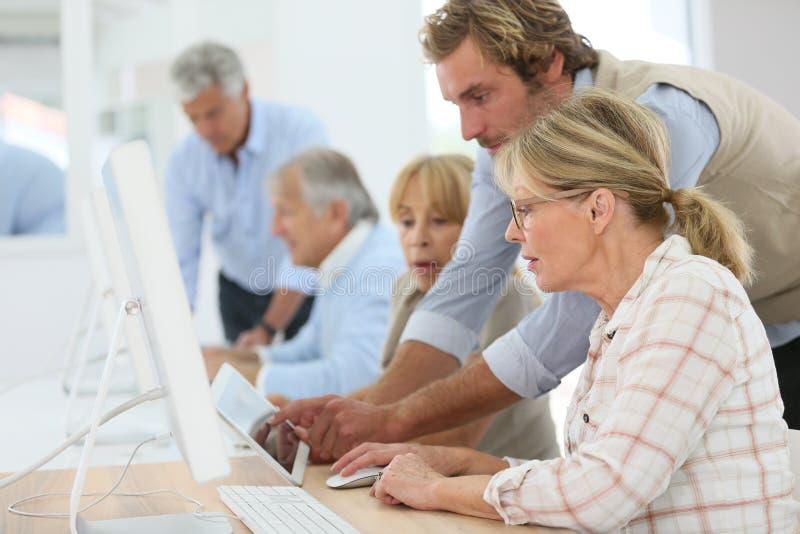Grupo de mayores que asisten a la clase computacional imágenes de archivo libres de regalías