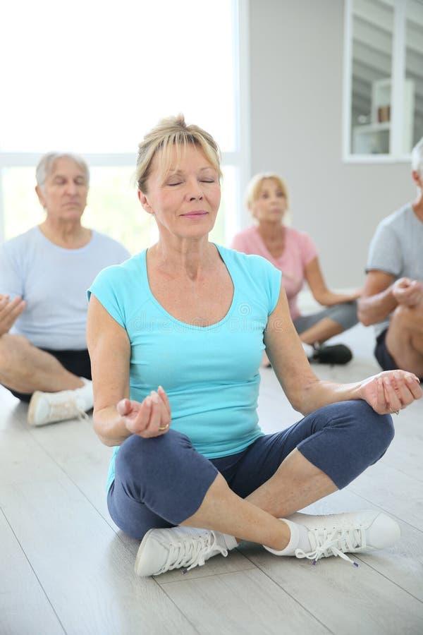 Grupo de mayores que hacen yoga de la meditación imagen de archivo libre de regalías