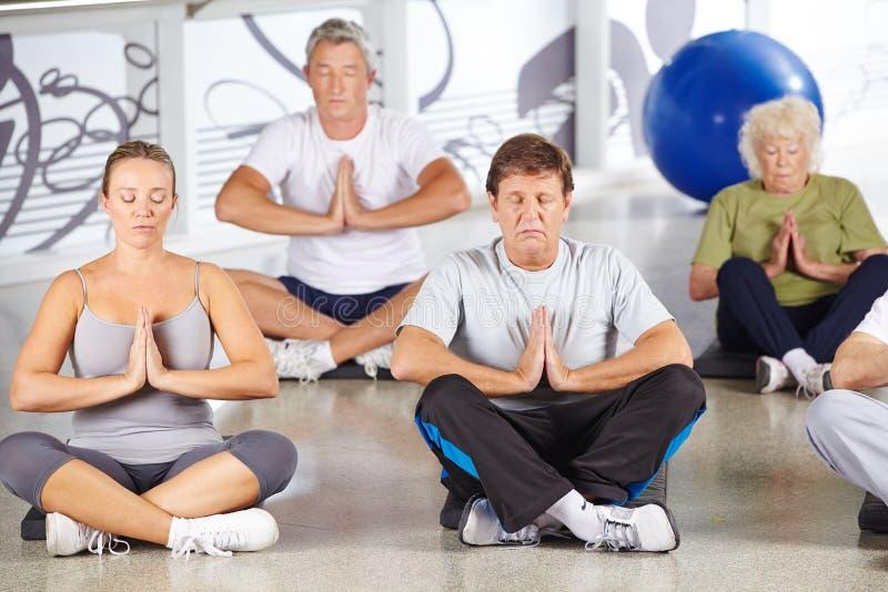 Grupo de mayores que hacen yoga en el centro de aptitud fotografía de archivo