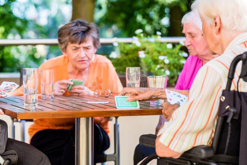 Grupo de mayores que juegan al juego de mesa en la terraza de la casa de retiro imagen de archivo