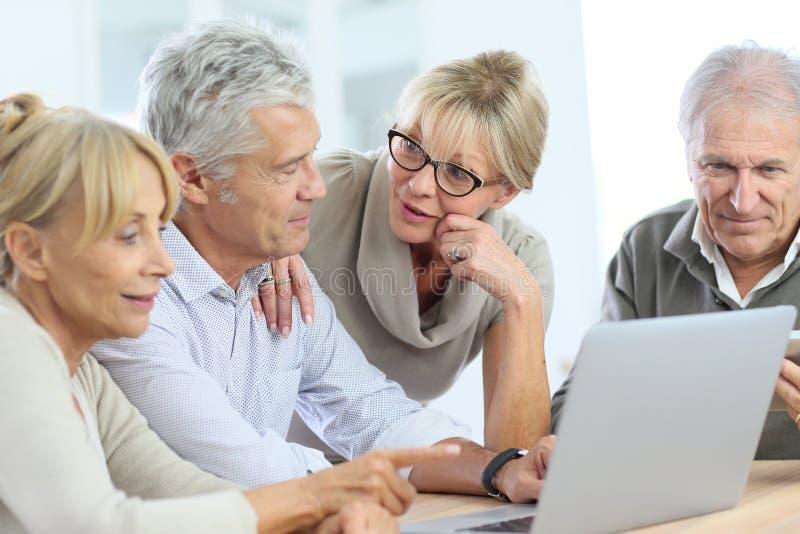 Grupo de mayores que usan el ordenador portátil y hablar fotografía de archivo libre de regalías