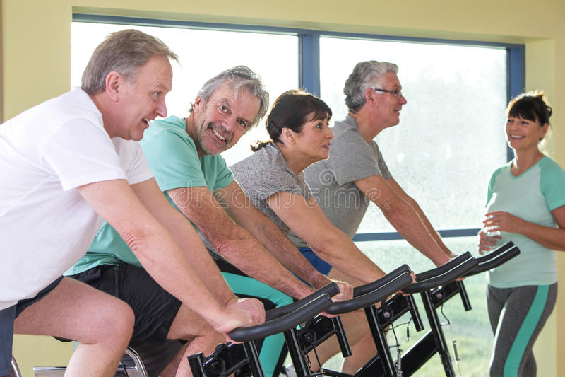 Grupo de mayores que usan las bicis de giro imagen de archivo libre de regalías