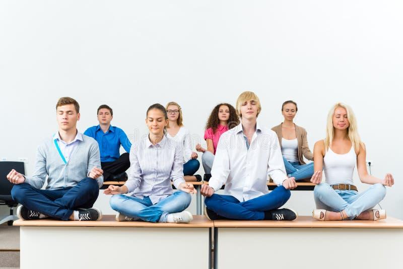 Grupo de meditar dos jovens fotos de stock