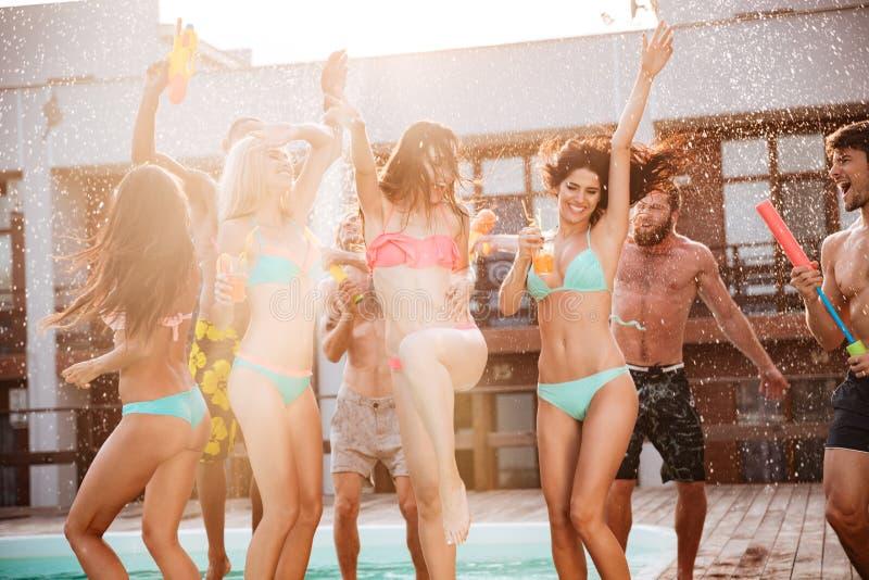 Grupo de mejores amigos que tienen baile de la diversión en la piscina foto de archivo libre de regalías