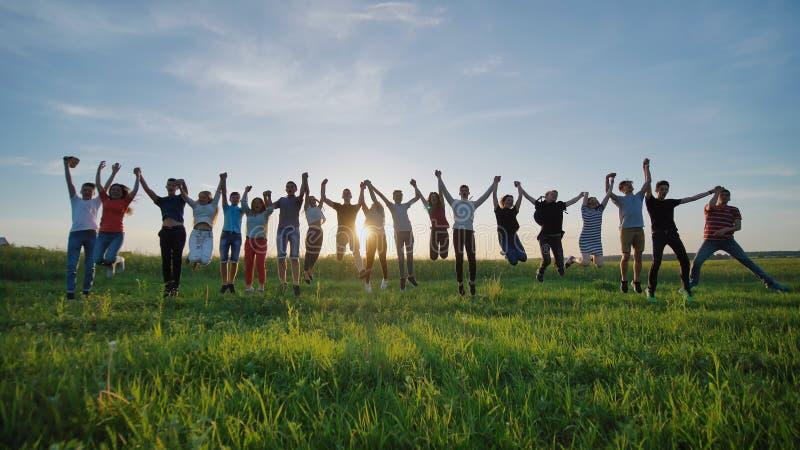 Grupo de mejores amigos y de estudiantes que saltan al aire libre Puesta del sol con los rayos de la sol imagenes de archivo