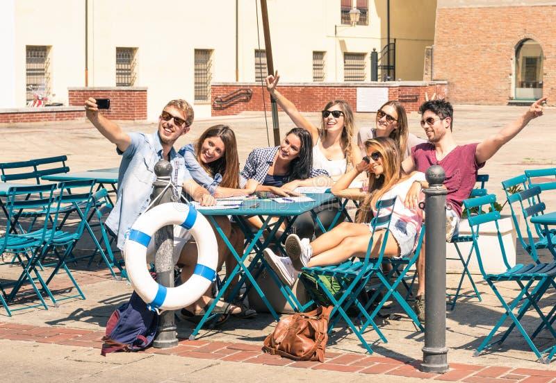 Grupo de melhores amigos felizes dos estudantes que tomam um selfie fotos de stock
