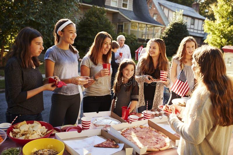 Grupo de meninas adolescentes que falam sobre a tabela do alimento em uma festa do quarteirão imagens de stock royalty free