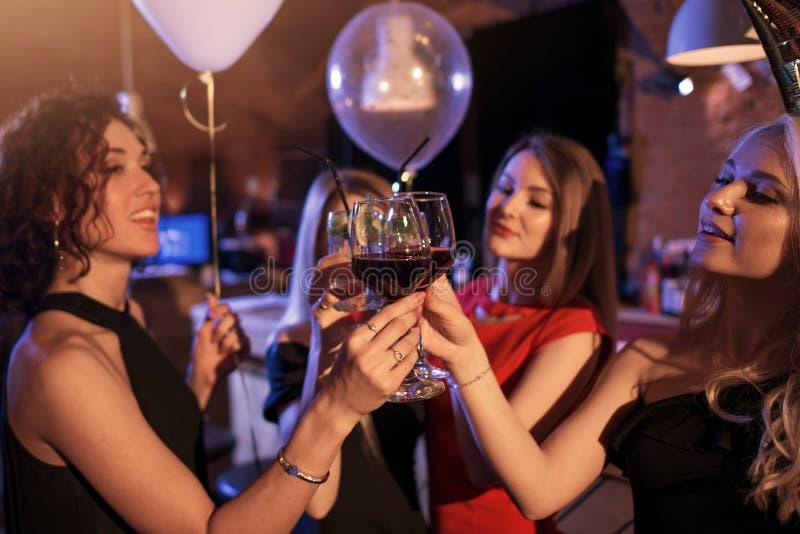 Grupo de meninas alegres que têm vidros eretos de um tinido do partido junto no clube noturno fotos de stock