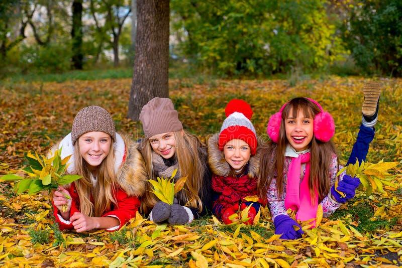 Grupo de meninas no parque do outono com folhas fotos de stock