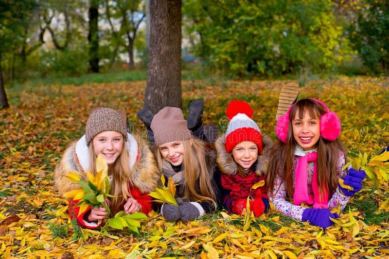 Grupo de meninas no parque do outono com folhas imagens de stock royalty free