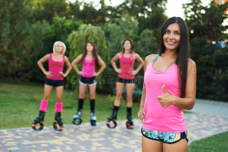 Grupo de meninas que fazem exercícios em botas de salto do kangoo Exercício exterior da aptidão Uma menina sorri em olhares in ca imagens de stock royalty free