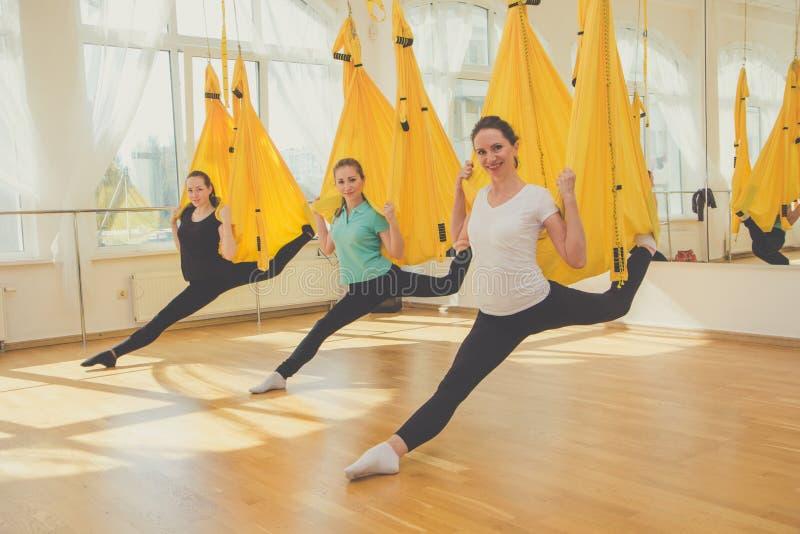Grupo de meninas que fazem a ioga da mosca nas redes fotografia de stock