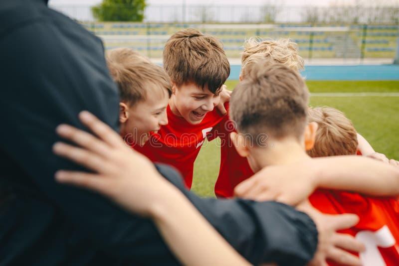 Grupo de meninos felizes que fazem a aproxima??o dos esportes Crian?as de sorriso que est?o junto com o treinador no campo de esp fotos de stock