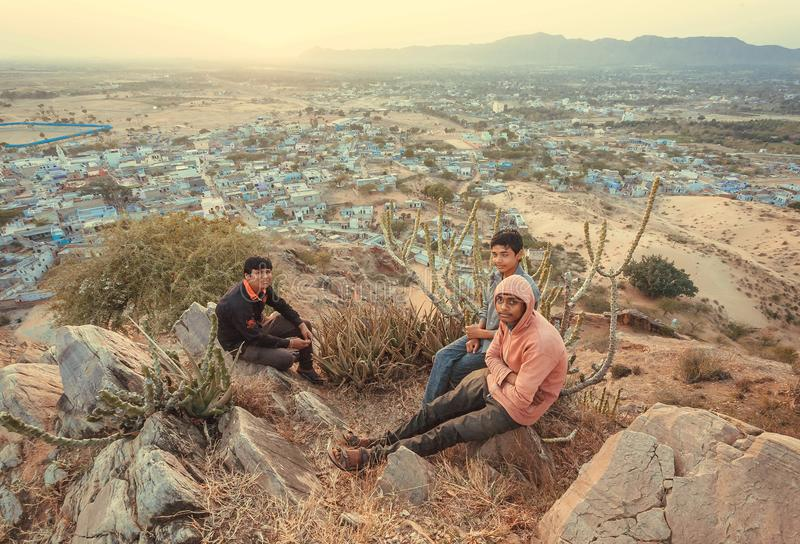 Grupo de meninos novos que relaxam na parte superior do monte com grande landcape, acima da cidade índia fotografia de stock
