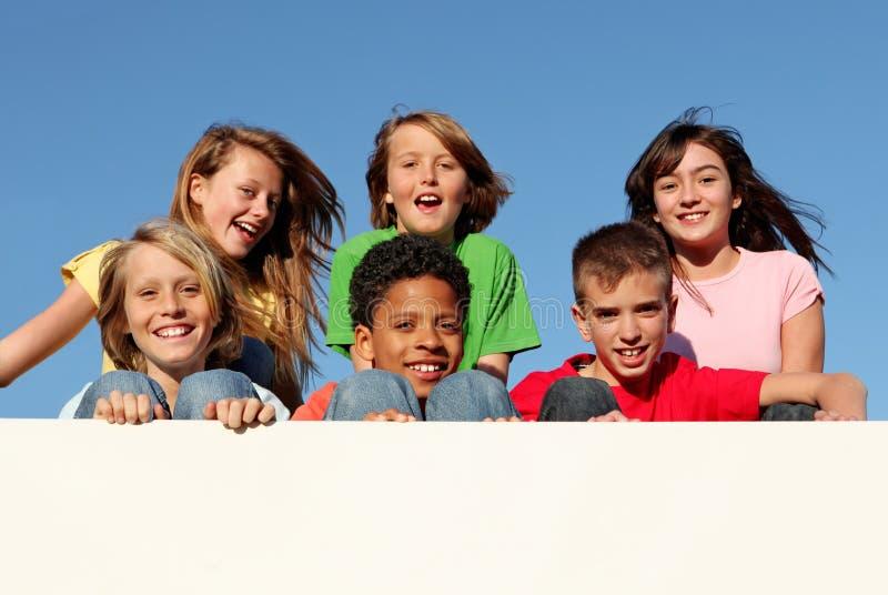 Grupo de miúdos com sinal ou a bandeira em branco imagens de stock royalty free