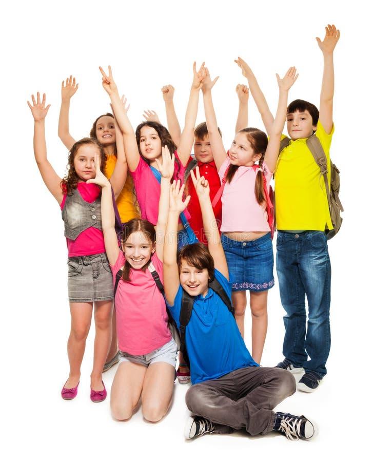 Grupo de miúdos felizes que levantam as mãos imagens de stock royalty free