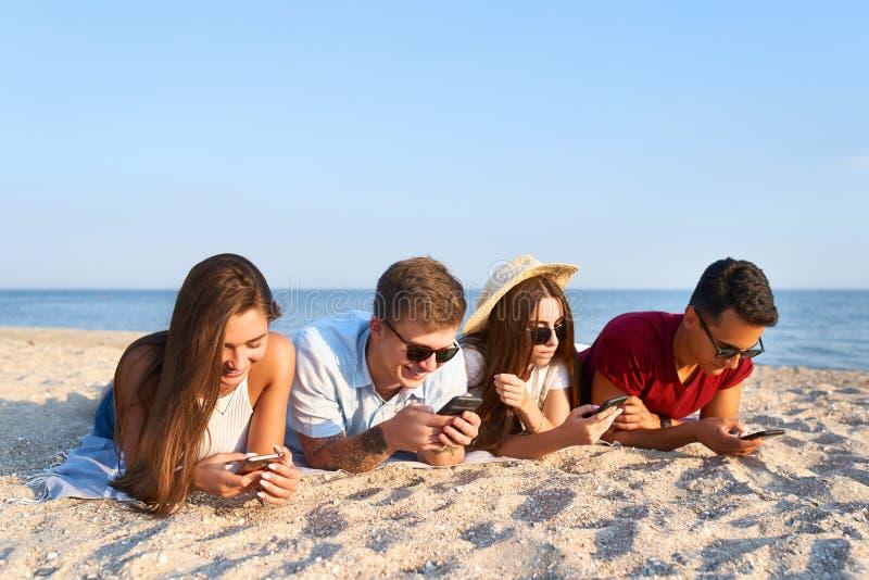 Grupo de millenials usando os smartphones que colocam junto na toalha de praia perto do mar no por do sol do verão Os jovens dedi fotos de stock royalty free