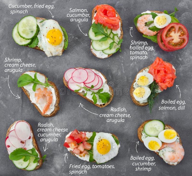 Grupo de mini sanduíches no fundo de pedra cinzento foto de stock royalty free