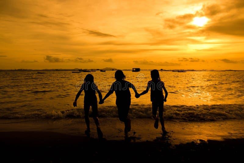 Grupo de moça feliz que corre na praia na soma bonita fotografia de stock