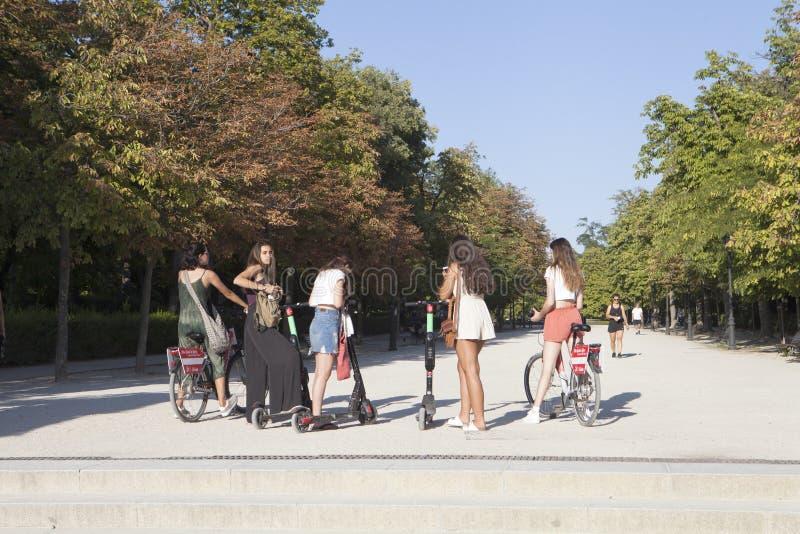 Grupo de moças com 'trotinette's e as bicicletas elétricos no parque de Retiro imagens de stock royalty free