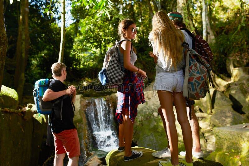 Grupo de mochileiros em Tailândia que olha a cachoeira da selva foto de stock