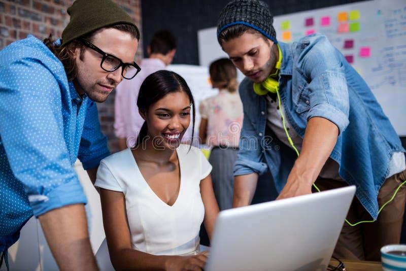 Grupo de modernos que usam um computador foto de stock