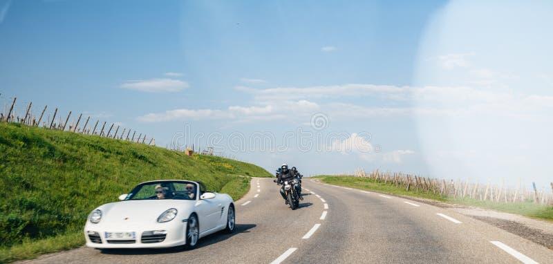 Grupo de motociclista que seguem os pares que conduzem em Porsche branca imagens de stock royalty free